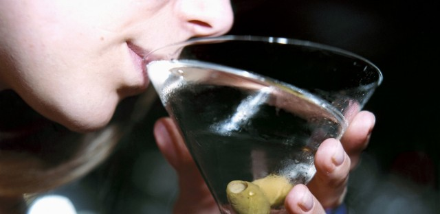 A woman drinks a martini