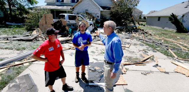 Illinois Gov. Bruce Rauner, right, talks with Bryan Phelan, left, and neighbor John Halloran in the driveway of Phelan's storm damaged home Tuesday, June 23, 2015, in Coal City, Ill., after a tornado passed through the area.