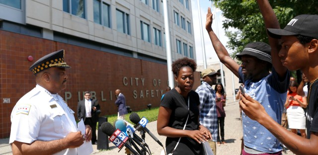 Chicago Police Superintendent Eddie Johnson, left, is blocked by three protestors as he tries to deliver a written statement about the recent release of police shooting video to television reporters outside the police department headquarters Friday, Aug. 5, 2016, in Chicago. (AP Photo/Tae-Gyun Kim)