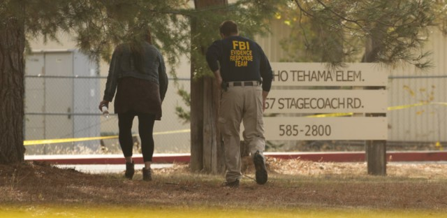 An FBI agent scans the area outside Rancho Tehama Elementary School after the shooting Tuesday. Four people were killed and many others injured when a gunman went on a rampage across Rancho Tehama, Calif., earlier in the day.