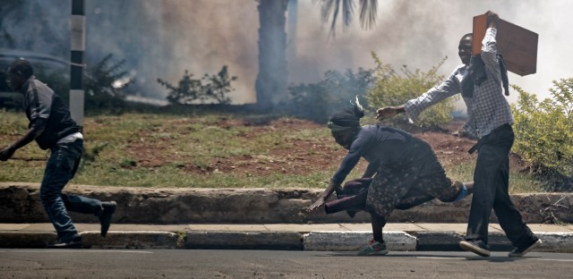 A passerby stumbles to the ground as she and opposition supporters, protesting over the upcoming elections, run for safety amid a cloud of tear gas fired by riot police in downtown Nairobi, Kenya Monday, Oct. 16, 2017.