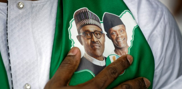 A supporter of incumbent President Muhammadu Buhari, wearing a sticker of Buhari and and Vice President Yemi Osinbajo, stands for the national anthem at a campaign rally in Abuja, Nigeria Wednesday, Feb. 13, 2019. Nigeria is due to hold general elections on Saturday, Feb. 16, 2019.