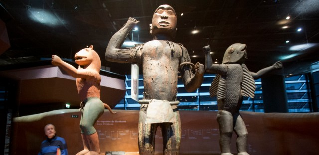 Visitors look at wooden royal statues of the Dahomey kingdom, dated 19th century, today's Benin, at the Quai Branly museum in Paris, France, Friday, Nov. 23, 2018. From Senegal to Ethiopia, artists, governments and museums are eagerly awaiting a report commissioned by French President Emmanuel Macron on how former colonizers can return African art to Africa.