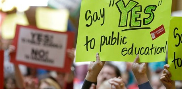 A supporter for public education holds up a sign during a rally at the Statehouse Tuesday, March 19, 2013, in Indianapolis. Opponents of a proposal to expand Indiana's private school voucher program rallied at the Statehouse to make their case that the vouchers hurt traditional public schools.