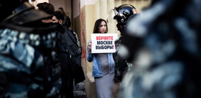 """A woman holds a poster reading """"Give us back our elections in Moscow!"""" in front of police during a protest in Moscow, Russia, Saturday, Aug. 10, 2019. Some thousands of people rallied Saturday against the exclusion of some city council candidates from Moscow's upcoming election, turning out for one of the Russian capital's biggest political protests in years. After the rally, which was officially sanctioned, hundreds of participants streamed to an area near the presidential administration building to continue with an unauthorized demonstration."""