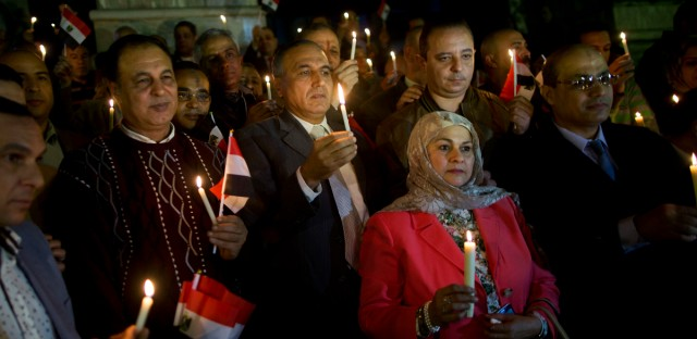 People take part during a candlelight vigil as they hold national flags for victims of a Friday mosque attack at the Journalists Syndicate, in Cairo, Egypt, Monday, Nov. 27, 2017.