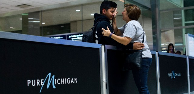 From left, Bryan Quintana-Salazar, 13, cries as his former teacher, Jennifer Walsh, of Ann Arbor, wipes tears from his face before he enters the security line with his family to travel to Mexico on Tuesday, August 1, 2017 at the Detroit Metropolitan Airport in Romulus, Michigan. Lourdes Salazar Bautista (not pictured), took her two younger children with her to Mexico as she was deported.