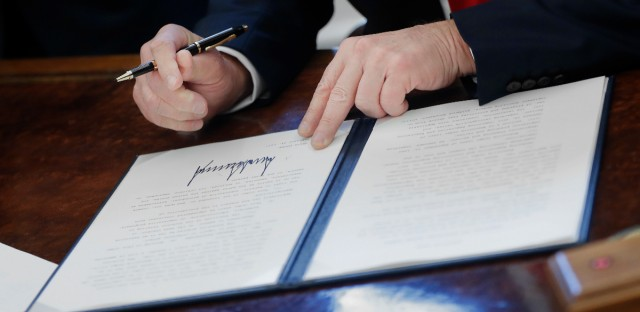 President Donald Trump signs an executive order in the Oval Office of the White House in Washington, Friday, Feb. 24, 2017. The executive order would establish regulatory reform officers and task forces within federal agencies a part of his push to slash federal government regulations.
