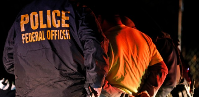 U.S. Immigration and Customs Enforcement agents detain a person during an Oct. 22, 2018 raid in Richmond, Va. (AP Photo/, File)