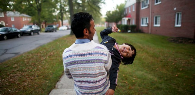 """Omar Al-Awad holds his daughter as they walk home in Toledo, Ohio, where they were recently resettled after fleeing Syria and living in a Jordanian refugee camp. From the story """"Among The Lucky Few: Syrian Family Rebuilds In America's Heartland,"""" 2015."""