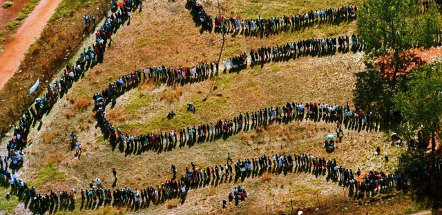 Long lines of people queue outside a polling station to cast their votes in South Africa's