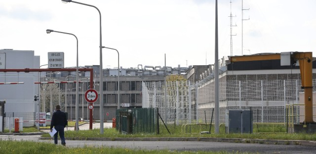 A man walks toward the high-security prison of Fleury-Merogis where Salah Abdeslam, the suspect in the Paris attacks, was bing held outside Paris, Thursday, April 28, 2016.