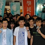Hong Kong activists, from left to right, Nathan Law, Joshua Wong and Alex Chow chant slogans outside the high court before a ruling on a prosecution request for stiffer sentences in Hong Kong, Thursday, Aug. 17, 2017.