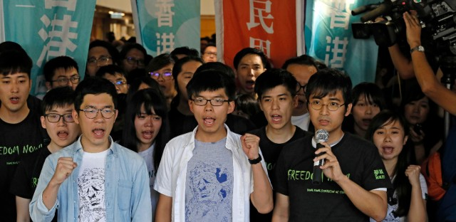 "Hong Kong's ""Umbrella Movement"" activists, from left to right, Nathan Law, Joshua Wong and Alex Chow chant slogans outside the high court before a ruling on a prosecution request for stiffer sentences in Hong Kong, Thursday, Aug. 17, 2017."