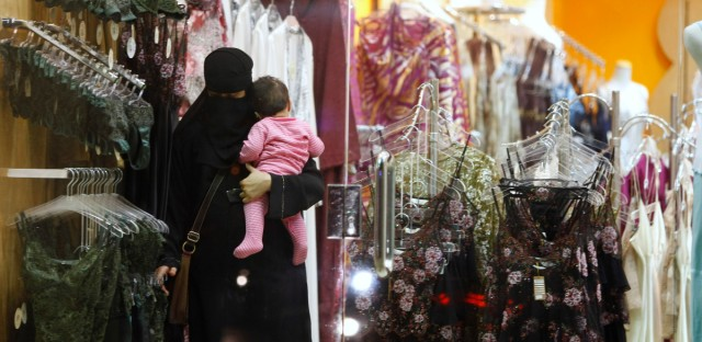 A Saudi woman holding a child checks out lingerie at a store in Riyadh, Saudi Arabia in 2009, when only men were allowed to sell underwear in almost all stores in the ultraconservative kingdom.