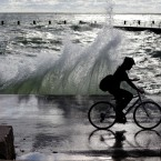 A commuter rides on a bike path along the shore of Lake Michigan Tuesday, Aug. 13, 2013, in Chicago.