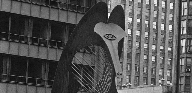 A few hours after the death in France of artist Pablo Picasso, a woman walks through Chicago's Civic Center Plaza past the largest rendering of any of his works on April 8, 1973. The design for the unnamed sculpture was donated to Chicago by Picasso and unveiled in August 1967. It is constructed of rusty steel, stands five stories tall, and weighs 160 tons.