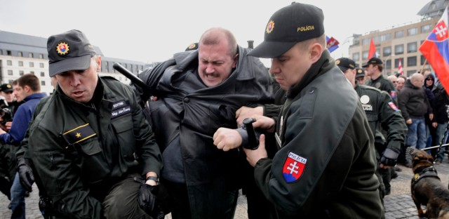 Slovak police officers detain Marian Kotleba, center, leader of officially banned association Slovak Togetherness, during a rally in Bratislava, Saturday, March 14, 2009. Some 300 people gathered in downtown Bratislava to mark the 70th anniversary of the independent Nazi-sponsored Slovak State.