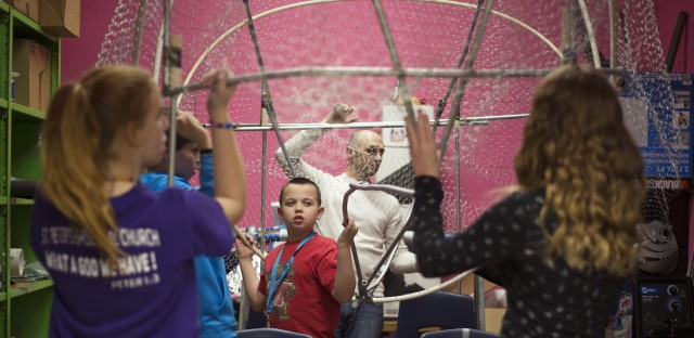 Teacher Michael Guarraia helps members of the Arbutus Middle School Kinetic Club place the frame of their brain sculpture in the classroom closet.
