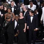 """Barry Jenkins, foreground left, and the cast accept the award for best picture for """"Moonlight"""" at the Oscars on Sunday at the Dolby Theatre in Los Angeles."""