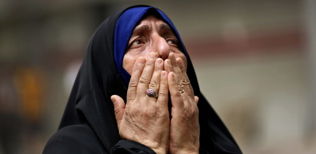In this Sunday July 3, 2016, file photo, an Iraqi woman grieves at the scene after a truck bomb attack in Karada, a busy shopping district in the center of Baghdad, Iraq. As millions of Muslims around the world celebrate the end of Ramadan, many are struggling to come to grips with what has been a particularly bloody month of attacks that killed more than 350 people and spread terror across continents.