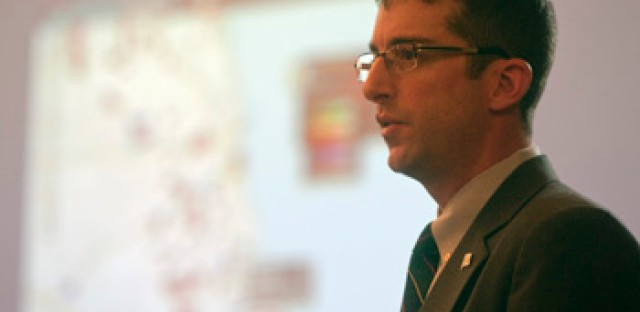 Brett Goldstein, the commissioner and chief data officer for the Department of Innovation and Technology, addresses a group of academics, developers and urban planners in February. Behind him, is a picture of a program dubbed WindyGrid.