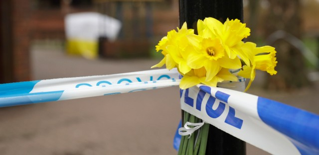 Daffodils are placed by a police cordon backdropped by a tent covering the area where former Russian double agent Sergei Skripal and his daughter were found critically ill following exposure to the Russian-developed nerve agent Novichok in Salisbury, England, Tuesday, March 13, 2018. (AP Photo/Matt Dunham)