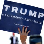 A supporter holds a sign as Republican presidential candidate Donald Trump speaks during a campaign rally in Arizona.