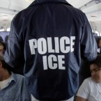 An Immigration and Customs Enforcement (ICE) agent walks down the aisle of charter jet for deportation in the air between Chicago and Harlingen, Texas. Under legislation proposed in the city of Evanston plans, police and other city employees would be prevented from asking people about their immigration status and reporting undocumented immigrants to the federal government.