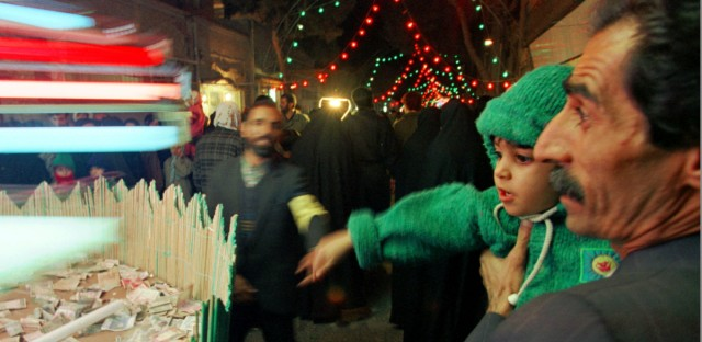 "A father holds his child as they toss a coin donation for the local mosque during a celebration in a southern Tehran neighborhood, Dec. 16, 1997. The celebration was in honor of the birthday of Imam Mahdi, or ""Hidden Imam,"" a 9th century saint that Shiite Muslims believe will return at the end of the time to restore justice to the world."