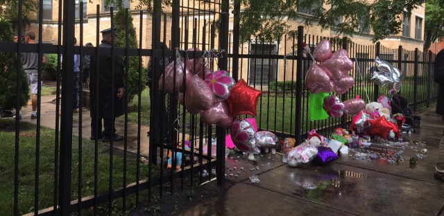 A makeshift memorial sits outside of the South Side apartment where a fire killed four people on Monday.