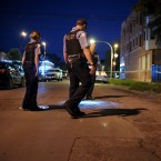Chicago police officers search the scene after local residents said five shots were fired into a crowd of teenagers in the 1600 block of West 57th Street on Saturday.