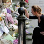 A woman lays flowers for the victims of the Manchester Arena attack in central Manchester, England, on Tuesday.