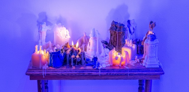 An art piece featuring wax candles of well-known American monuments by Sandy Williams IV, whose work is included in the 'Shut Up Stone Mountain' exhibition.