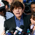 "Former Illinois Gov. Rod Blagojevich speaks to the media outside his home in Chicago as his wife, Patti, wipes away tears a day before he was to report to a prison after his conviction on corruption charges. On Monday federal prosecutors said statements Blagojevich has made prove he isn't ""deserving of leniency."" A resentencing hearing is scheduled next month for Blagojevich, who is hoping a federal judge will give him a five-year sentence instead of his original 14 years."