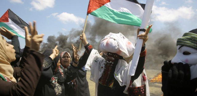 Palestinian women wave national flags and chant slogans near the Israeli border fence, east of Khan Younis, in the Gaza Strip, Monday, May 14, 2018.