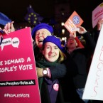 Anti-Brexit demonstrators react after the results of the vote on British Prime Minister Theresa May's Brexit deal were announced in Parliament square in London, Tuesday, Jan. 15, 2019. British lawmakers have rejected Prime Minister Theresa May's Brexit deal by a huge margin, plunging U.K. politics into crisis 10 weeks before the country is due to leave the European Union. The House of Commons voted 432 -202 on Tuesday against the deal struck between Britain's government and the EU in November.