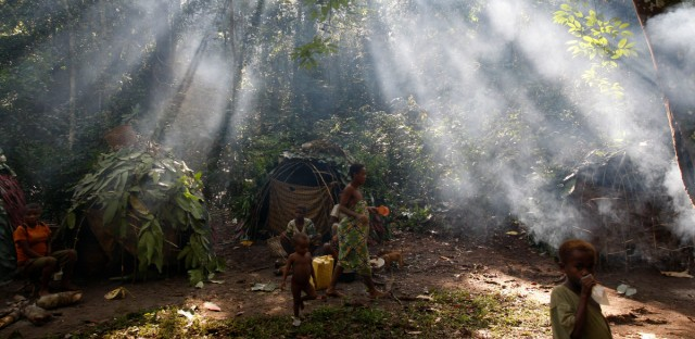 Shafts of sunlight filtering through the forest canopy strike smoke from fires burning outside family huts at an Mbuti pygmy hunting camp in the Okapi Wildlife Reserve outside the town of Epulu, Congo.