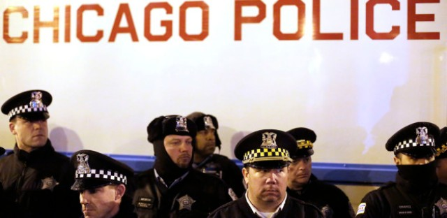 Chicago police officers surround a police vehicle as they watch demonstrators protesting the fatal police shooting of Laquan McDonald December 18 in Chicago, Illinois.