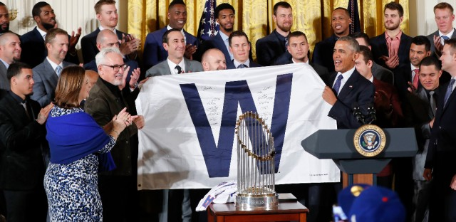 President Barack Obama holds up a 'W' flag signed by the Cubs during a ceremony