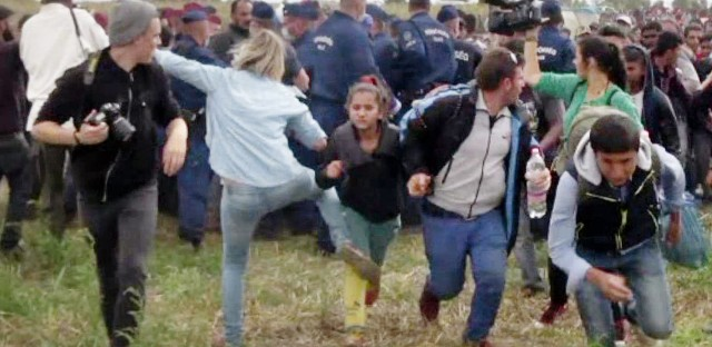 A video grab from Sept. 9, 2015, shows Petra Laszlo, a Hungarian camerawoman, kicking a child running with other migrants from a police line in southern Hungary. She also tripped Osama Abdul Mohsen, running with son Zaid in his arms.
