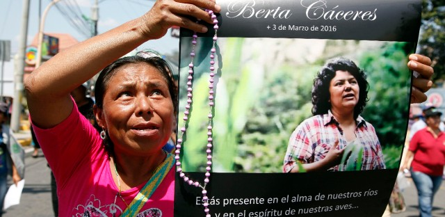 """A woman holds up a poster with a photo of slain environmental leader Berta Caceres, during a protest march in Tegucigalpa, Honduras, Wednesday, March 16, 2016. Authorities said that unidentified gunmen killed Nelson Garcia, a colleague of Caceres, who was slain almost two weeks ago in similar circumstances. The organization that both Caceres and Garcia belonged to is describing Garcia's death as part of """"the government's constant harassment"""" of Indian groups. Both activists were Lenca Indians and belonged to the Indian Council of People's Organizations of Honduras."""