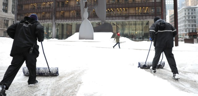 Chicago was hit with about 5 inches of snow overnight. Workers shovel walkways at Chicago's Daley Plaza.