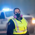 Smoke fills the air as a police officer stands guard at a roadblock along Highway 63 leading into Fort McMurray on Sunday.