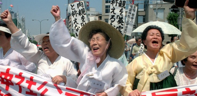 Raising clenched fists, South Korea's former comfort women shout slogans and march in downtown Tokyo Tuesday, Aug. 15, 1995, marking the 50th anniversary of the end of World War II. Former sex slaves of Japanese Imperial Army are demanding compensation to the Japanese government. At center with hat is Kang Soo-ae. Others are not identified.