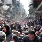 In this Jan. 31, 2014 file photo released by the United Nations Relief and Works Agency for Palestine Refugees in the Near East (UNRWA), shows residents of the besieged Palestinian camp of Yarmouk, queuing to receive food supplies, in Damascus, Syria.