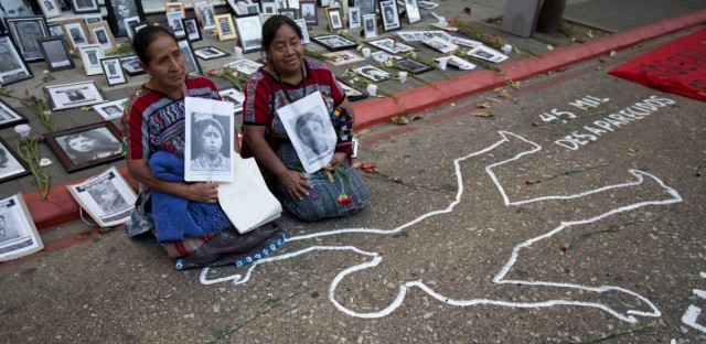 Carmen Cumes, left, and Rosalina Tuyuc, of the National Coordination of Guatemalan Widows (CONAVIGUA), sit surrounded by portraits of people who are disappeared as a form of protest outside Congress in Guatemala City, Wednesday, March 13, 2019. Lawmakers postponed the approval of a controversial bill that could give amnesty to the perpetrators of war crimes dating back to the country's bloody civil war.