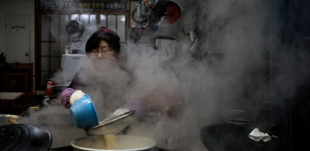 A woman cooks at a restaurant in Gangneung, South Korea, Monday, Feb. 12, 2018.