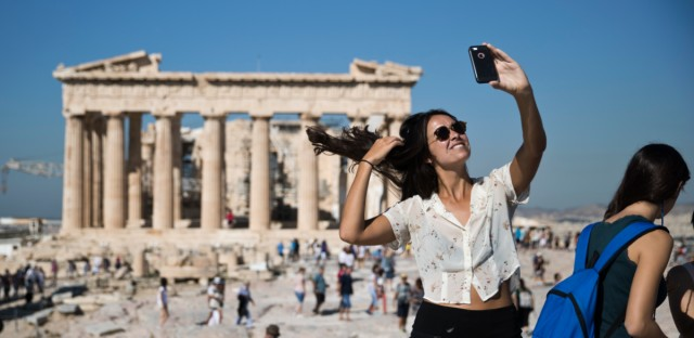 A tourist takes a selfie in front of the the ruins of the fifth century B.C. Parthenon temple at the Acropolis hill, on Friday, Sept. 1, 2017.
