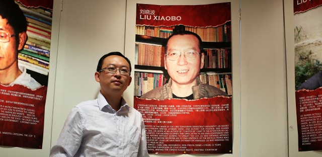 Chinese author Yu Jie, shown here in 2012 in Washington, D.C., with a poster of 2010 Nobel Peace laureate Liu Xiaobo, says he was kidnapped, tortured and forced to promise in writing not to criticize China's top leaders.